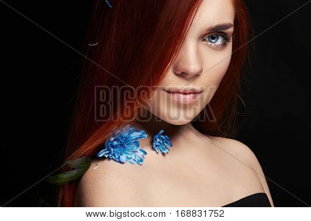 Sexy beautiful redhead girl with long hair. Perfect woman portrait on black background. Gorgeous hair and deep eyes. Natural beauty clean skin facial care and hair. Strong and thick hair. Flower