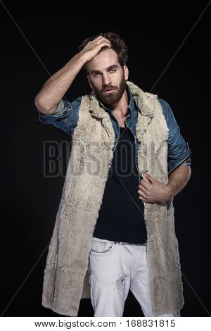 Young Handsome Bearded Man In Fur Waistcoat And Denim Shirt Posing On Dark Background