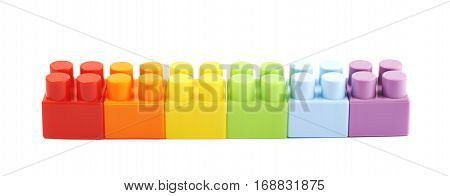 Line of plastic construction and rainbow colored toy bricks isoalted over the white background