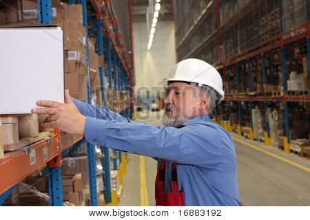 older worker in uniform putting heavy box on  shelf in warehouse