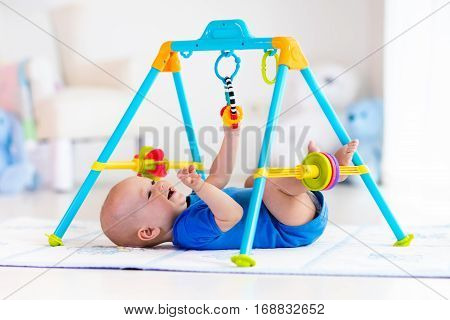 Baby Boy On Play Mat. Child Playing In Gym.