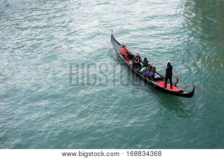 Venice Italy - October 16 2016:Tourists on a typical gondola in a Venetian canal with gondolier with typical dress