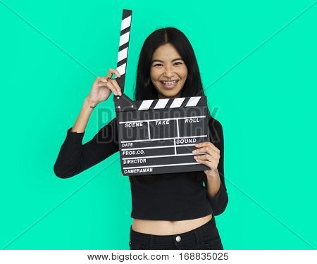 Young woman in croptop holding clapperboard