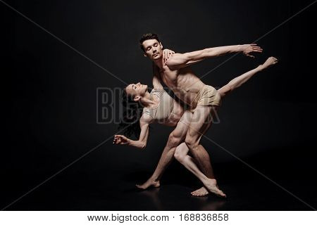 Stretching before the performance. Skillful concentrated involved ballet dancers dancing in the studio and expressing grace and inspiration while demonstrating their skills and stretching