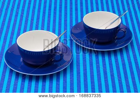 Symmetry arrangement empty cups of tea on blue striped tablecloth. Blue concept.