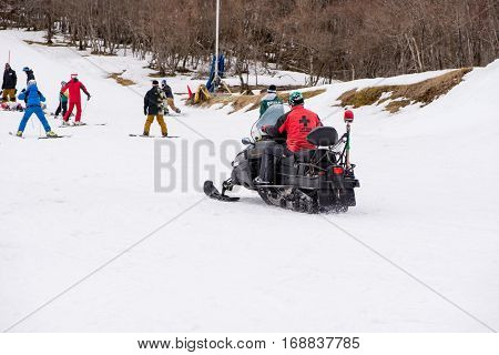 February 4 2017. A paramedic rides on a snowmobile to a snowboarding tourist injured in an accident. Gokase ski area Miyazaki Japan.