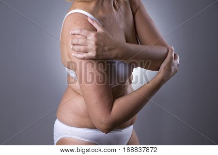 Pain in shoulder care of female hands ache in woman's body on gray background