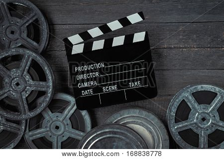 Clapperboards and reel of film lie on the old board