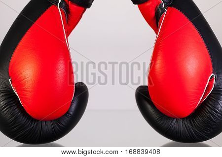 Red and black boxing gloves on a glass table isolated on white background