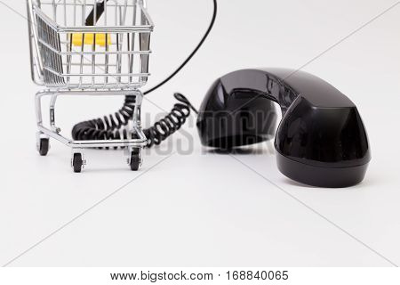 Old phone reciever and cord connection with shopping trolley. Shopping hotline concept.