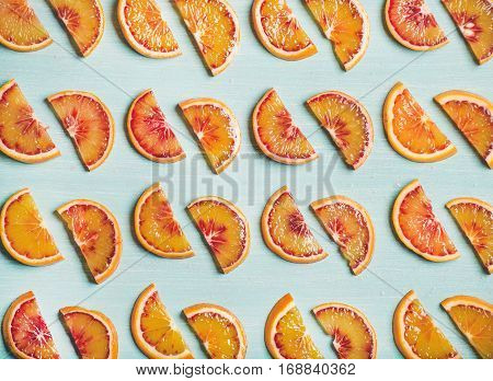 Natural fruit pattern concept. Fresh juicy blood orange slices over light blue painted table background, top view