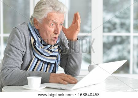 mature man using laptop, sitting near window