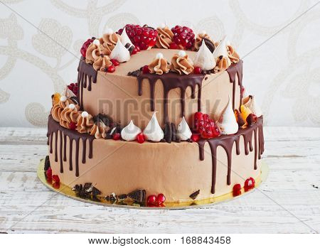 Festive two-tier cake with fruit with streaks of chocolate on a light background