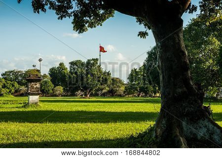 Hue, Vietnam - November 11, 2015: View over a lawn in Imperial Palace, vietnam flag waving in the background
