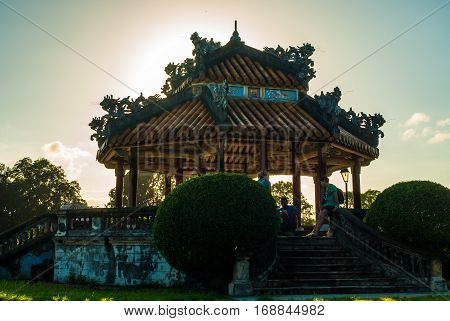 Hue, Vietnam - November 11, 2015: Pavilion with tourist sitting in the shade in direct afternoon light