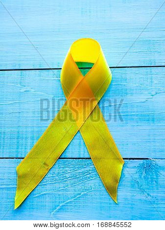 Childhood Cancer Day. Yellow Ribbon on blue background