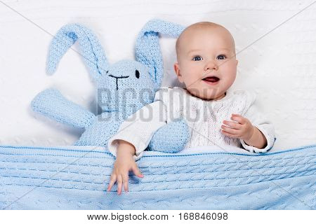 Baby Boy Playing With Bunny Toy In Bed