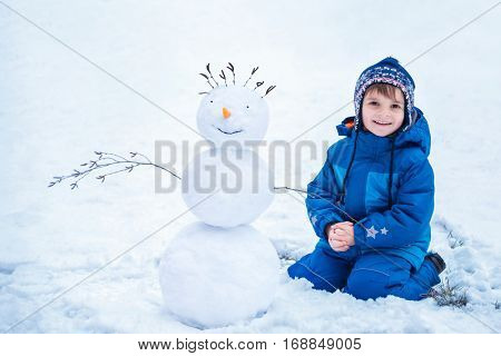 cute little boy sitting near the smiling snowman