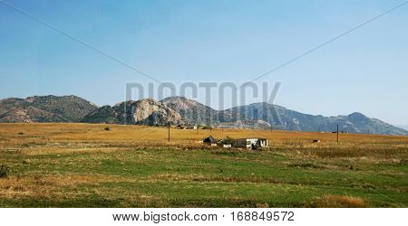 Single cottages and round huts of the Swazi in the high plain of Swaziland, barren landscape in autumn, in the background a mountain chaine