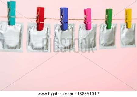 Condoms hanging on the rope on light pink background.