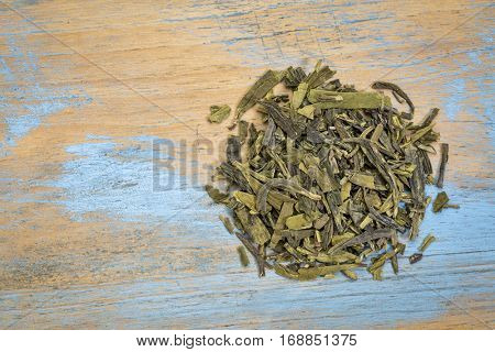 Dragonwell (Longjing) loose leaf green tea, a heap over grunge wood with a copy space, top view