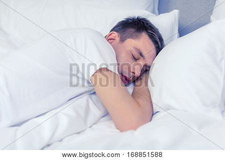 hotel, travel and happiness concept - handsome man sleeping in bed