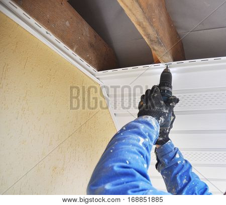 Constructor Install Soffit. Roofing Construction. Soffit and Fascia is Usually Constructed of Vinyl Wood or Aluminum and is Installed on the Underside of Roof Overhangs and Eaves