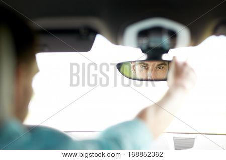 road trip, transport and people concept - man driving car adjusting rearview mirror