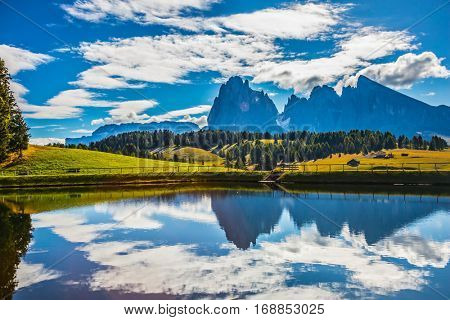 Wonderful small lake reflects the jagged rocks of the Dolomites. Well-known international ski resort in the fall. Concept of active and ecological tourism