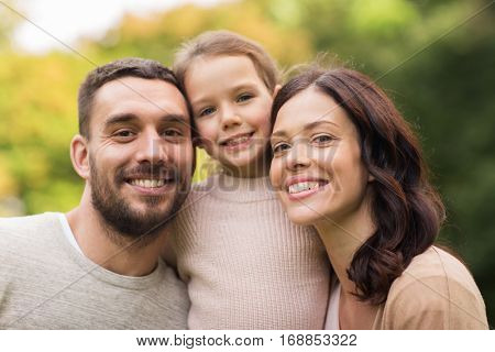 family, parenthood, adoption and people concept - happy mother, father and little girl in summer park