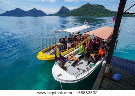 Semporna,Sabah-Sept 10,2016:Group of tourist arrived at Bohey Dulang jetty Semporna,Sabah with beautiful islands on  background.Bohey Dulang Island is one of the most popular & attraction islands in Tun Sakaran Marine Park.