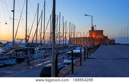 Mandraki Harbour Rhodes Greece and The Palace of the Grand Master of Knights of Rhodes at night.