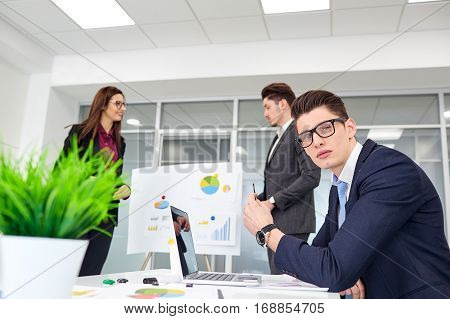 Man with glasses working in the office on  background of colleagues.