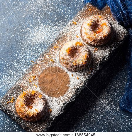 Mini bundt ring cakes with orange zest icing sugar on dark blue background and serving board. Top view. Holiday christmas sweet food