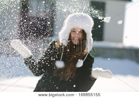 Girl playing with snow in park, background image.