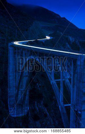Rich blue hour colorful Big Sur Bixby Creek Bridge lit by passing cars in the evening twilight landscape