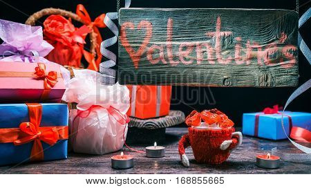 Gifts, heart candies and burning candles on gift store counter. Wood hanging sign. Valentine concept