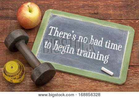 There is no bad time to begin training -  slate blackboard sign against weathered red painted barn wood with a dumbbell, apple and tape measure