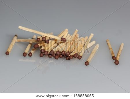 wooden matches scattered on a gray background