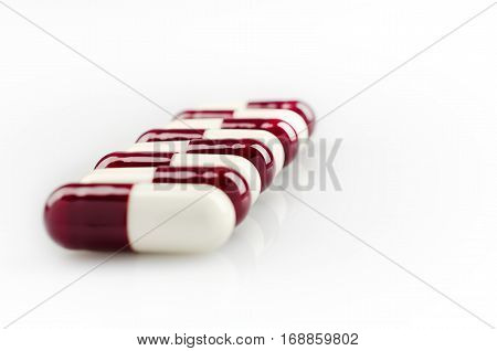 Medical theme. Dark red capsules on a white surface. Closeup