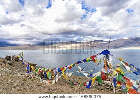 Prayer flags over Tso Moriri lake in Ladakh, India. A prayer flag is a colorful rectangular cloth, often found along mountain ridges and peaks in the Himalayas and are used to bless the surrounding
