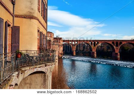 a view of the Tarn River as it passes through Albi, in France, with the Pont Neuf bridge in the background