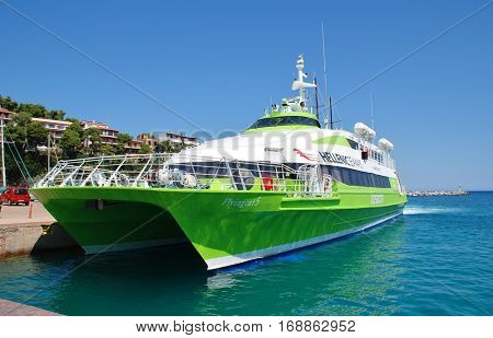 ALONISSOS, GREECE - JUNE 21, 2013: Hellenic Seaways catamaran ferry Flying Cat 5 docked at Patitiri harbour on the Greek island of Alonissos. The 39mtr vessel was built in 1996 in Norway.