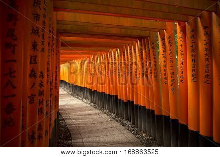 KYOTO, JAPAN - APRIL 13, 2015: The gates in the Fushimi Inari shrine in Kyoto, Japan.  Famous for his thousand of orange tori gates