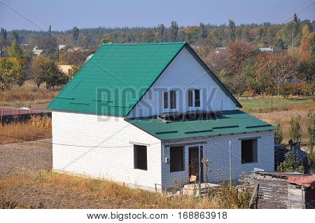 Building new white bricks country house with green metal roof with roof protection from snow board (Snow guard) on house construction