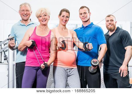 Group of people in gym with stretch bands and dumbbells
