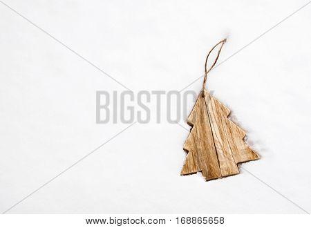 Wooden Christmas tree decoration on white snow