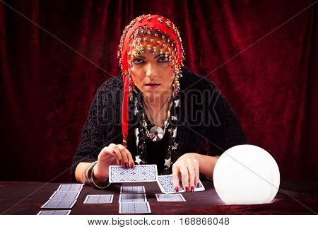 Studio shot of crazy fortune teller with tarot cards