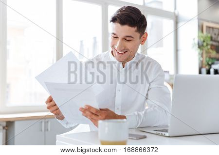 Photo of happy young man dressed in white shirt holding documents while using laptop computer. Coworking. Looking at documents.
