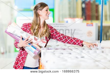 Young woman buying wallpapers in home improvement store